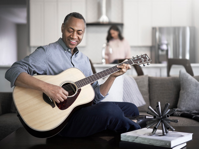 Man playing guitar with woman in the background
